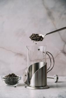 Vorderansichtschleifer, der mit teekräutern gefüllt wird