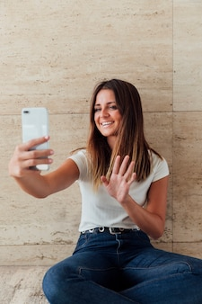Vorderansichtsmileymädchen, das am telefon wellenartig bewegt