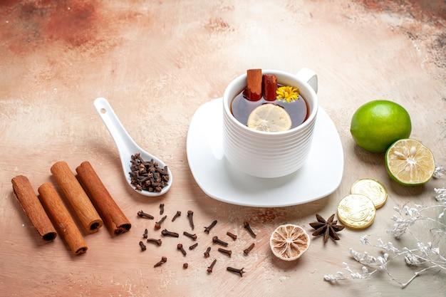 Vorderansichttasse tee mit zitrone und zimt auf hellbraunem tischzitronenkekstee