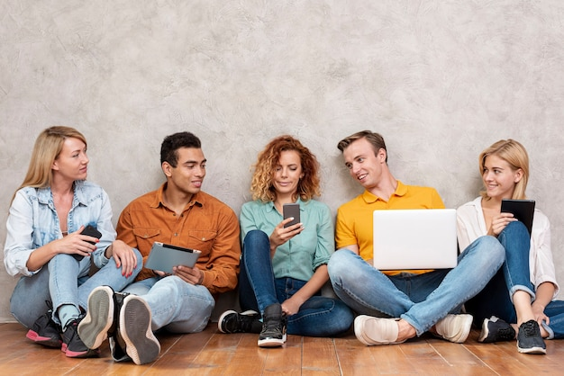 Vorderansichtunterweltler, die telefon sitzen und überprüfen