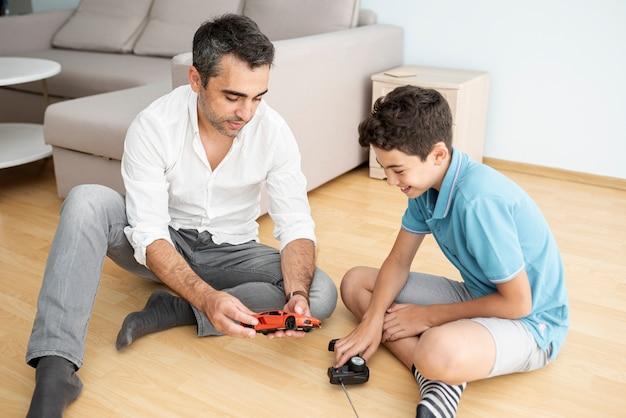 Vorderansichtvater und -kind, die mit einem elektroauto spielen