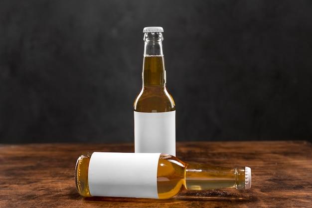 Vordere ansicht blonde bierflaschen mit leeren etiketten auf dem tisch