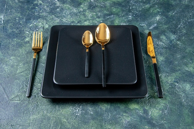 Vordere ansicht dunkle platten mit goldenen löffeln gabel und messer auf dunkelblauem hintergrund