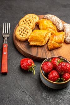 Vordere ansicht frische erdbeeren mit keksen und kuchen auf einer weißen oberfläche süßigkeiten süße frucht