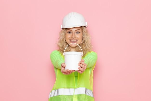Vordere ansicht junge baumeisterin im grünen bauanzughelm, der farbe mit lächeln auf dem rosa raum hält