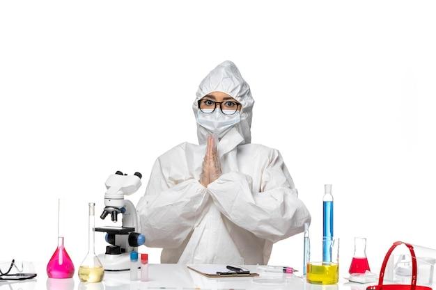 Vordere ansicht junge chemikerin in speziellem schutzanzug, der auf covid-chemie des weißen hintergrundviruslabors betet