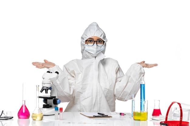 Vordere ansicht junge chemikerin in speziellem schutzanzug sitzend mit lösungen auf weißem hintergrundviruslabor covid health chemistry