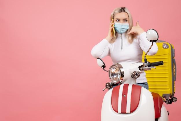Vordere ansicht junge dame auf moped mit gelbem koffer, der jemanden mit ihrem telefon anruft