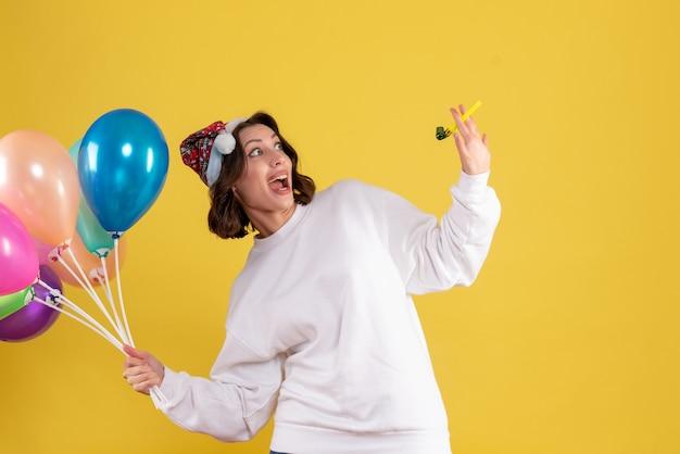Vordere ansicht junge frau, die ballons auf gelb hält