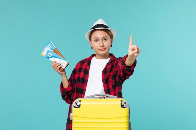 Vordere ansicht junge frau, die brieftasche mit tickets auf dem blauen raum hält