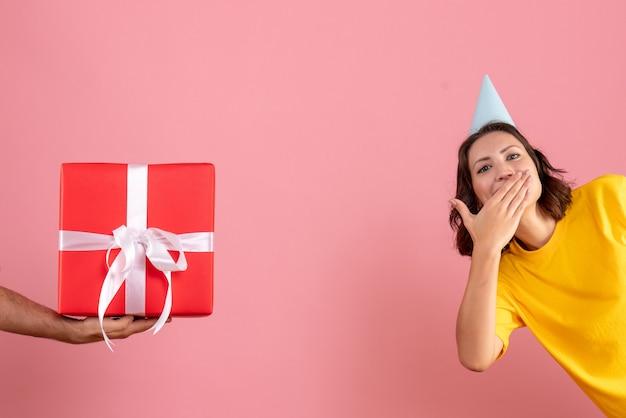 Vordere ansicht junge frau, die geschenk vom mann auf dem rosa annimmt