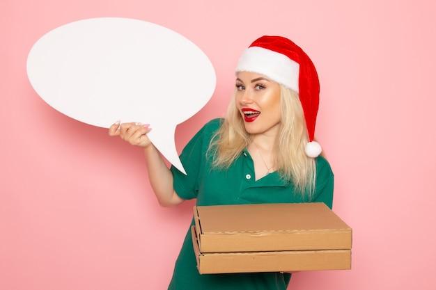Vordere ansicht junge frau, die großes weißes zeichen und nahrungsmittelkästen auf rosa wandfotoarbeitsuniform-neujahrsferienjob hält