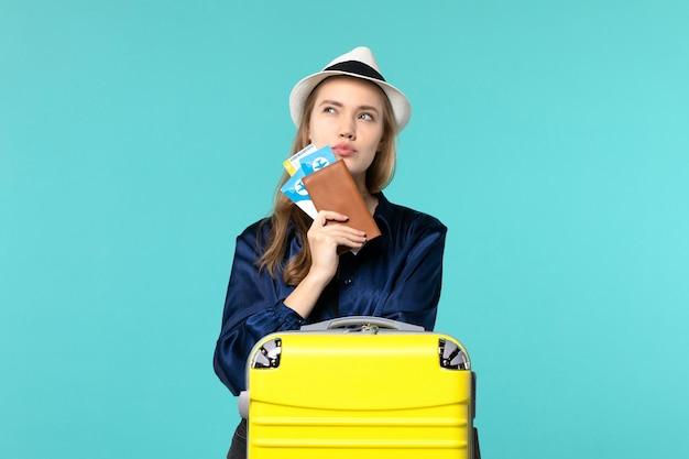 Vordere ansicht junge frau, die ihre tickets hält und sich auf reisendenken auf blauem hintergrundreiseflugzeug-seeurlaubsreise vorbereitet