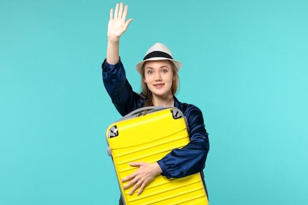 Vordere ansicht junge frau, die in den urlaub geht und große tasche hält, die jemanden auf blauem hintergrundreise-reiseferien-seereiseflugzeug begrüßt