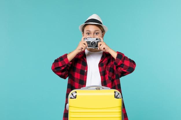 Vordere ansicht junge frau, die in reise geht und kamera auf blauem raum hält