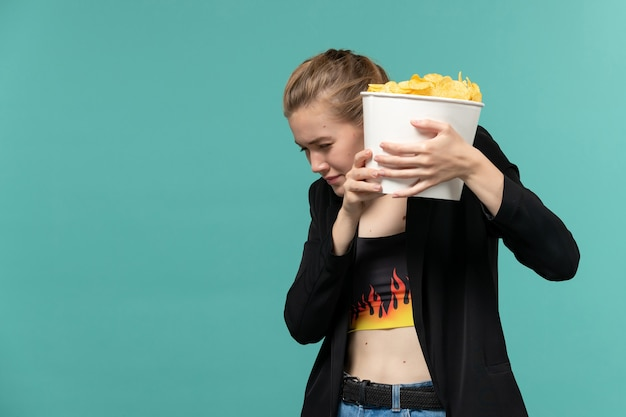 Vordere ansicht junge frau, die kartoffelchips isst, die film auf der blauen oberfläche sehen