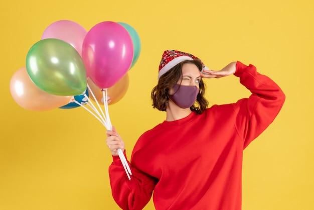 Vordere ansicht junge frau, die luftballons in der sterilen maske auf gelb hält