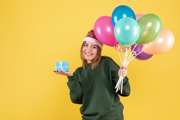 Vordere ansicht junge frau, die luftballons und wenig geschenk hält