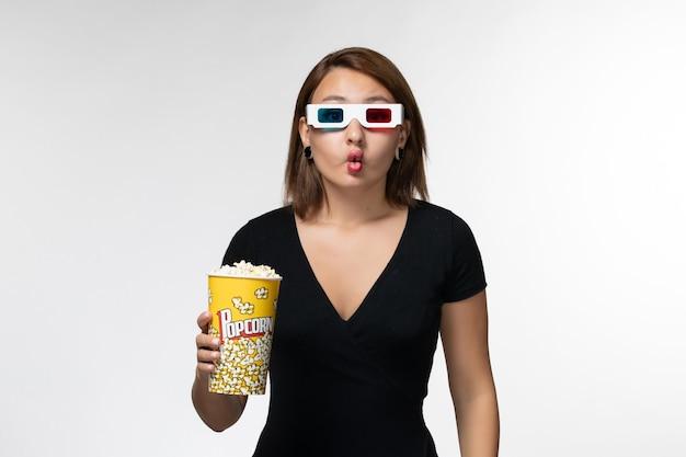 Vordere ansicht junge frau, die popcorn-paket in d sonnenbrille hält, die lustige gesichter auf weißer oberfläche macht