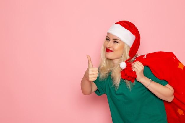 Vordere ansicht junge frau, die rote tasche mit geschenken auf dem rosa wandfeiertagsmodell weihnachten neujahrsfarbfoto santa trägt
