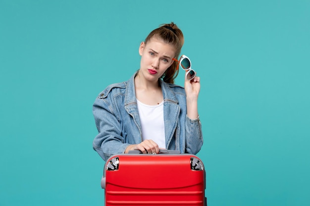Vordere ansicht junge frau, die sonnenbrille hält und sich auf urlaub auf blauem schreibtisch vorbereitet Kostenlose Fotos
