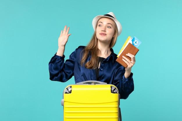 Vordere ansicht junge frau, die tickets hält und sich auf reise auf hellblauer hintergrundreise seeurlaubsreiseflugreise vorbereitet