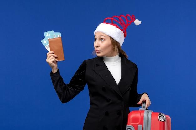 Vordere ansicht junge frau, die tickets mit tasche auf feiertagsflugzeugferien des blauen hintergrunds hält