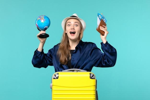 Vordere ansicht junge frau, die tickets und kleinen globus auf hellblauem hintergrundflugzeugurlaubsreisereise hält