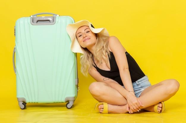 Vordere ansicht junge frau, die zusammen mit ihrer grünen tasche auf gelbem bodenausflugferiensonnenreise-reisemädchen sitzt