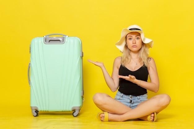Vordere ansicht junge frau, die zusammen mit ihrer grünen tasche auf gelber wandferiensonnenreisereise reise mädchen sitzt