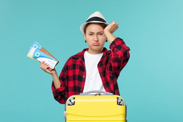 Vordere ansicht junge frau hält brieftasche mit tickets auf blauem boden urlaub seereise reise reise reisen