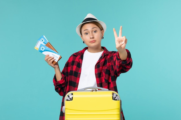 Vordere ansicht junge frau hält brieftasche mit tickets auf einem blauen boden urlaub seereise reise reisen