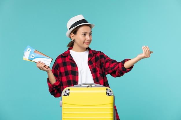 Vordere ansicht junge frau hält brieftasche mit tickets, die jemanden auf blauem raum anrufen
