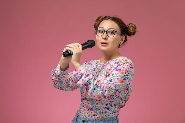 Vordere ansicht junge frau in blume entworfene hemdsonnenbrille, die mikrofon auf dem rosa hintergrund hält