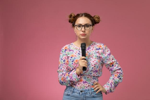 Vordere ansicht junge frau in blume entworfenes hemd, das versucht, mit mikrofon den rosa hintergrund zu unterzeichnen