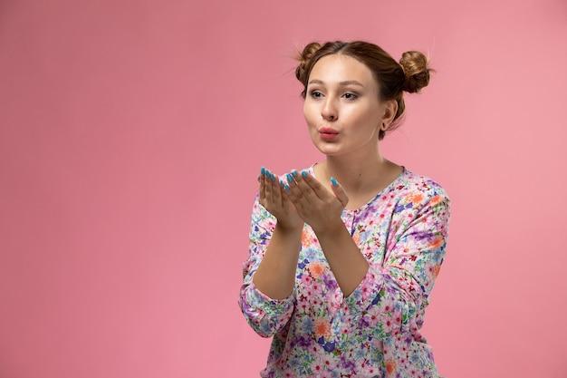 Vordere ansicht junge frau in blume entworfenes hemd und blaue jeans, die luftküsse auf dem rosa hintergrund senden
