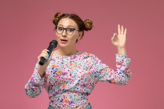 Vordere ansicht junge frau in blume entworfenes hemd und blaue jeans, die mikrofon halten versuchen, auf der rosa hintergrundmodellierung zu singen