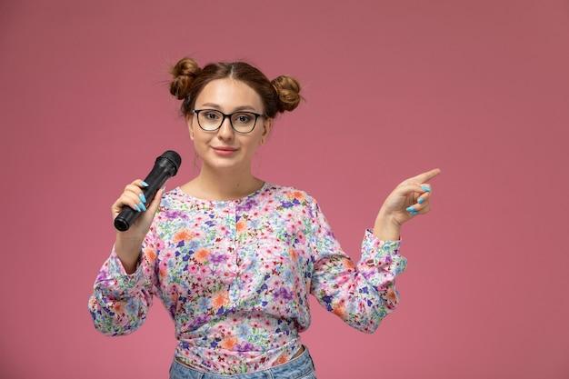 Vordere ansicht junge frau in blume entworfenes hemd und blaue jeans, die mikrofon halten versuchen, auf der rosa hintergrundmodellierungspose weiblich zu singen