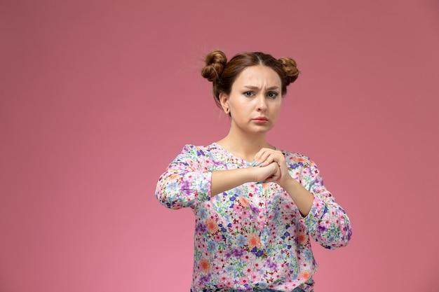 Vordere ansicht junge frau in blume entworfenes hemd und blaue jeans mit geballter faust, die auf dem rosa schreibtisch aufwirft