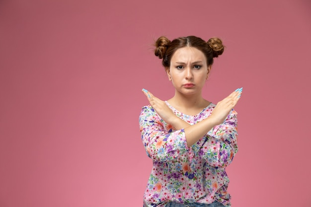 Vordere ansicht junge frau in blume entworfenes hemd und blaue jeans zeigen verbotszeichen auf dem rosa hintergrund