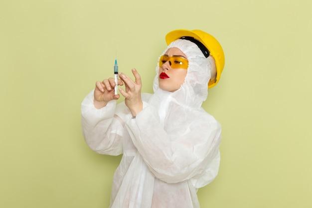 Vordere ansicht junge frau in weißem spezialanzug und gelbem helm, der injektion auf den grünraumchemie-arbeitsanzügen hält