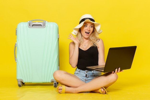 Vordere ansicht junge frau mit laptop auf gelbe wandreise urlaub weibliche reise reise sonne