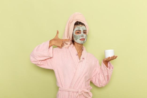 Vordere ansicht junge frau nach dusche im rosa bademantel, der creme auf grüner oberfläche hält