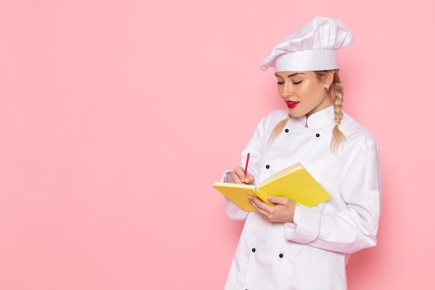 Vordere ansicht junge köchin im weißen kochanzug, die notizen in das heft auf dem rosa raumkoch aufschreibt