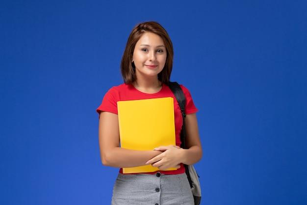 Vordere ansicht junge studentin im roten hemd mit rucksack, der gelbe dateien auf dem hellblauen hintergrund hält.