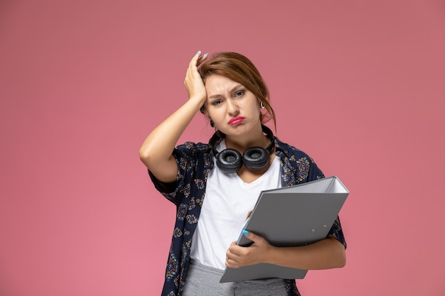 Vordere ansicht junge studentin im weißen t-shirt, das graue dokumente auf rosa hintergrundlektionsuniversitätshochschulstudienbuch hält