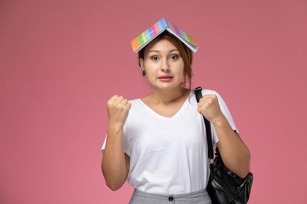 Vordere ansicht junge studentin im weißen t-shirt mit heft und entzücktem ausdruck auf rosa hintergrundlektion universitätsuniversitätsstudienbuch