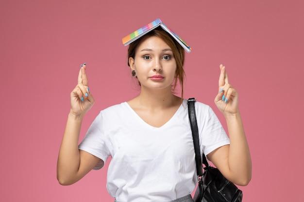 Vordere ansicht junge studentin im weißen t-shirt mit heft und tasche, die mit gekreuzten fingern auf rosa hintergrundlektionsuniversitätshochschulstudienbuch aufwirft