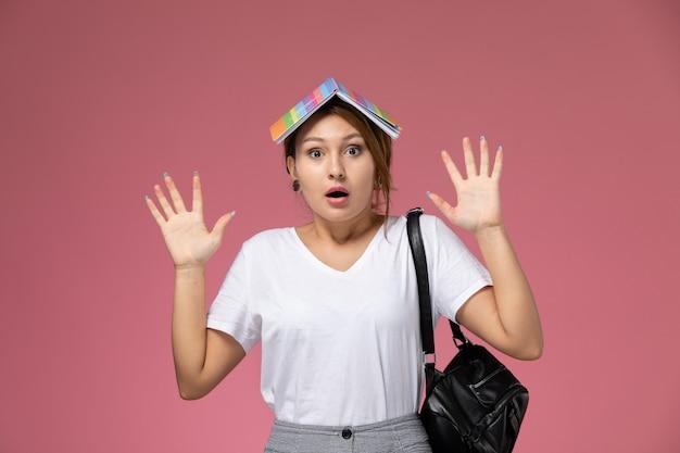 Vordere ansicht junge studentin im weißen t-shirt mit heft und tasche, die mit schockiertem ausdruck auf rosa hintergrundlektionsuniversitätshochschul-studienbuch aufwirft