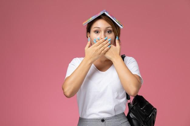 Vordere ansicht junge studentin im weißen t-shirt mit heft und tasche, die mit überraschtem ausdruck auf rosa hintergrundlektionsuniversitätsuniversitäts-studienbuch aufwirft
